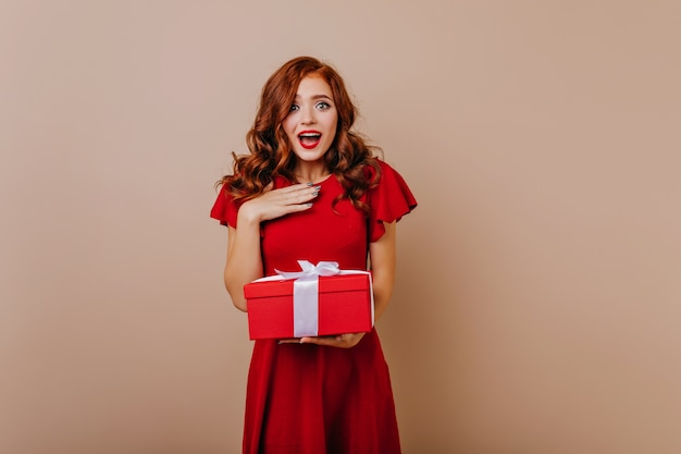プレゼントを持っている赤いドレスで驚いた女性。誕生日を祝う魅力的な生姜の女の子。