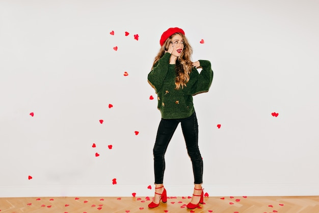 ハートの紙吹雪の下に立っている赤いサンダルとベレー帽で驚いた女性
