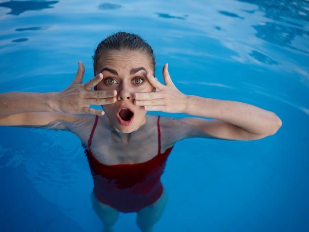 顔のプールの休息の近くに赤い水着の手で驚いた女性