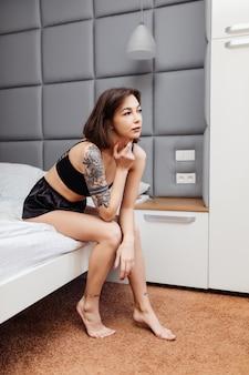 Удивленная женщина в сексуальной черной пижаме сидит на краю кровати в своей светлой комнате