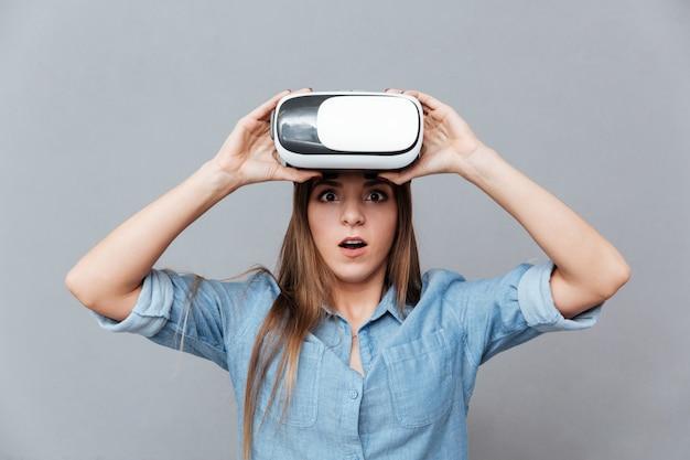 Удивленная женщина в рубашке снимает устройство виртуальной реальности