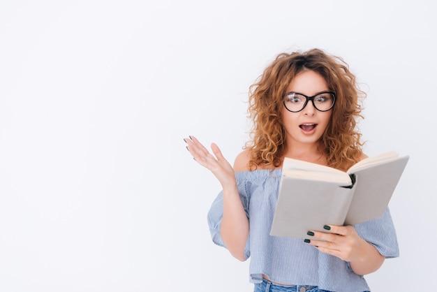 Удивленная женщина в синглетной и очках, читая книгу в студии. изолированный серый фон