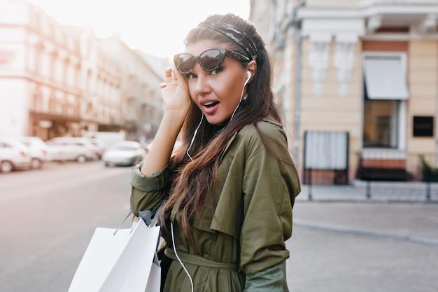 Удивленная женщина в стильной куртке, держащая солнцезащитные очки на городской стене