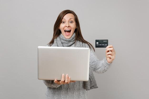 스웨터를 입은 놀란 여성, 랩톱 컴퓨터에서 작업하는 입을 벌린 스카프, 회색 배경에 격리된 신용 은행 카드를 들고 있습니다. 건강한 라이프 스타일 온라인 치료 컨설팅 추운 계절 개념.