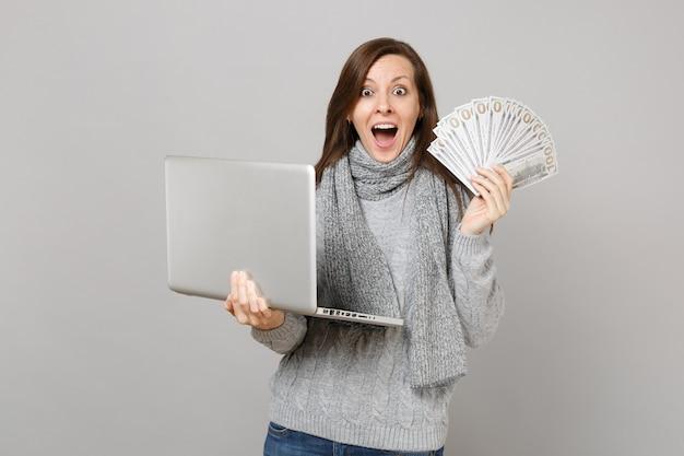 Удивленная женщина в свитере, работающем на портативном компьютере, держит много кучу долларов, банкноты, наличные деньги, изолированные на сером фоне. консультации по лечению здорового образа жизни онлайн в холодное время года.