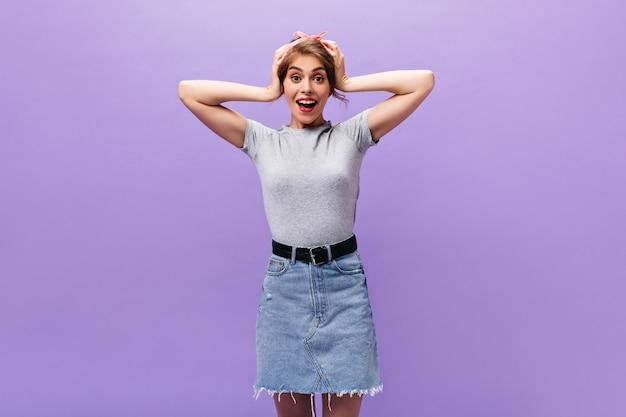 Tシャツを着た驚いた女性がカメラを覗き込む。紫色の背景に笑みを浮かべて広い黒帯とデニムスカートの幸せな美しい女性。