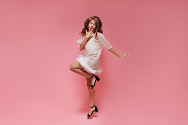 Удивленная женщина в белом платье прыгает по розовой стене
