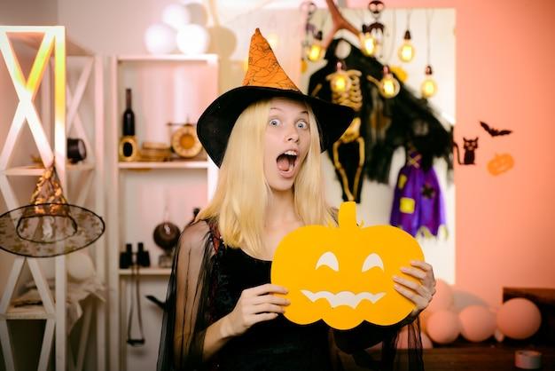 Удивленная женщина в шляпе ведьмы и коротком платье. вампир хэллоуин женский портрет. красивая молодая удивленная женщина в шляпе ведьмы и костюме, держащем тыкву. смешное лицо. сумасшедшие люди.
