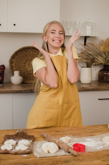 Surprised woman in the kitchen in an apron. confectioner, cook or housewife. cooking concept