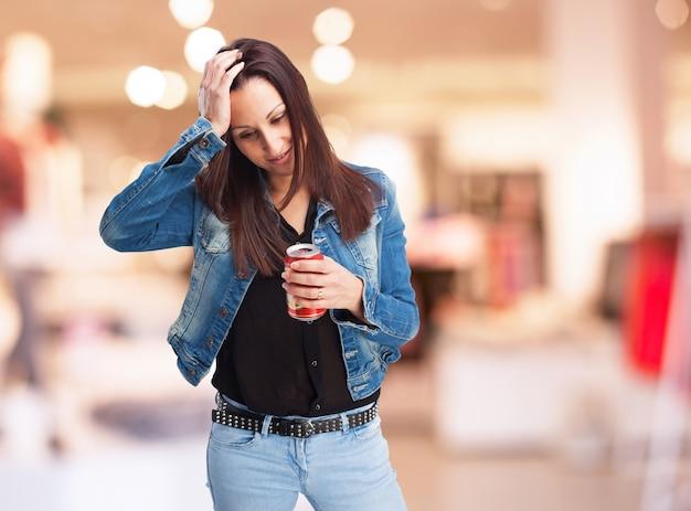 Удивленная женщина смотрит на банку соды