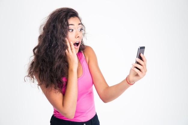 Удивленная женщина, смотрящая на смартфон