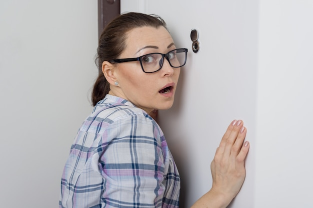 Surprised woman looks at the peephole of the front door in the apartment