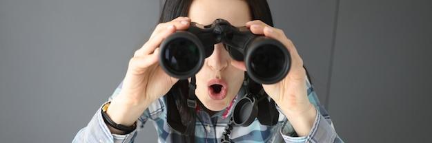 놀란 여자가 입을 벌리고 검은색 전문 쌍안경을 들여다본다
