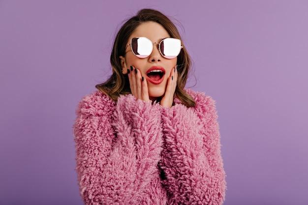 Удивленная женщина позирует в стильных блестящих очках