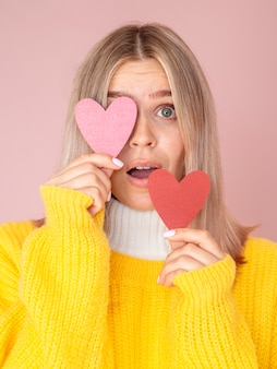 Surprised woman posing with paper hearts