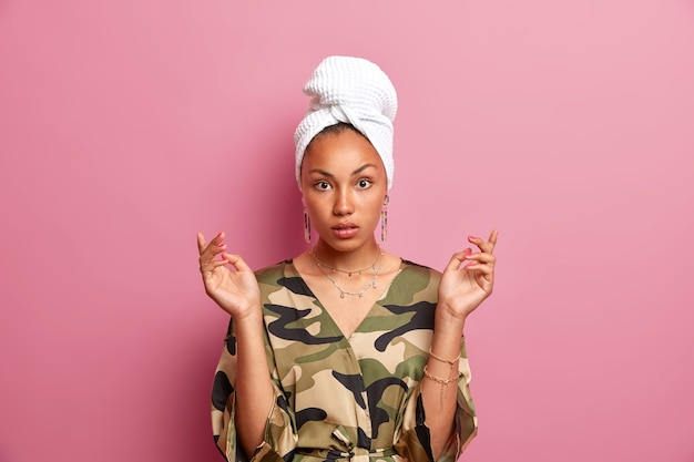 Surprised woman raises hands focused has healthy smooth dark skin wears dressing gown and wrapped towel on head after taking shower isolated over pink wall being at home alone