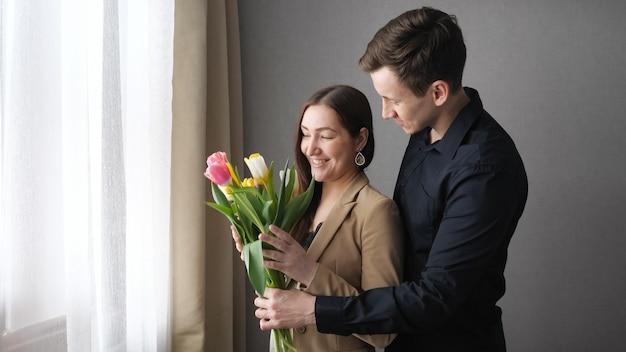 Удивленная женщина получает от возлюбленного цветы тюльпана.