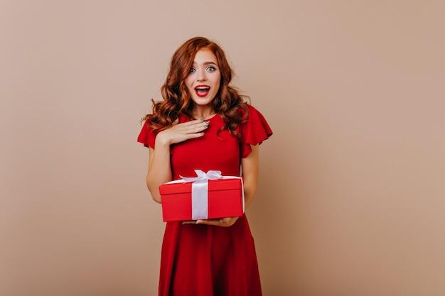 Donna sorpresa in vestito rosso che tiene i regali. ragazza attraente dello zenzero che celebra il compleanno.