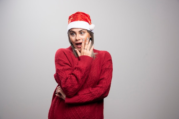 Surprised woman in santa hat standing on gray background.