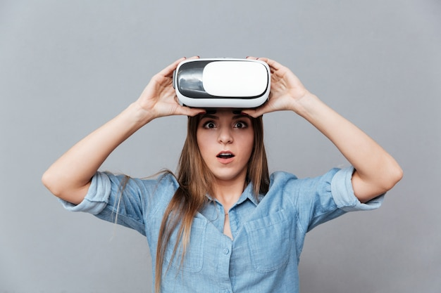 Surprised woman in shirt takes off virtual reality device