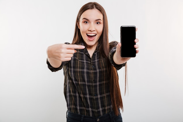 Surprised woman showing blank smartphone screen