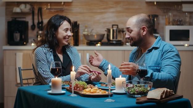 그녀의 남편에게 긍정적인 임신 테스트를 보여주는 놀란 여자. 이 좋은 소식에 대해 서로 웃고, 껴안고, 키스하는 흥분된 커플. 임신한 젊은 아내는 남자를 포용한 결과에 만족합니다.