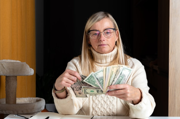 놀란 여자는 테이블에 앉아 달러 지폐를보고 적립 돈을 즐기고
