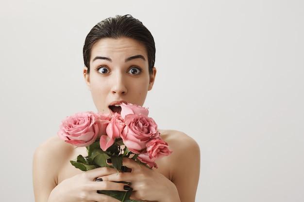 Donna sorpresa in piedi nuda e tenendo il mazzo di rose
