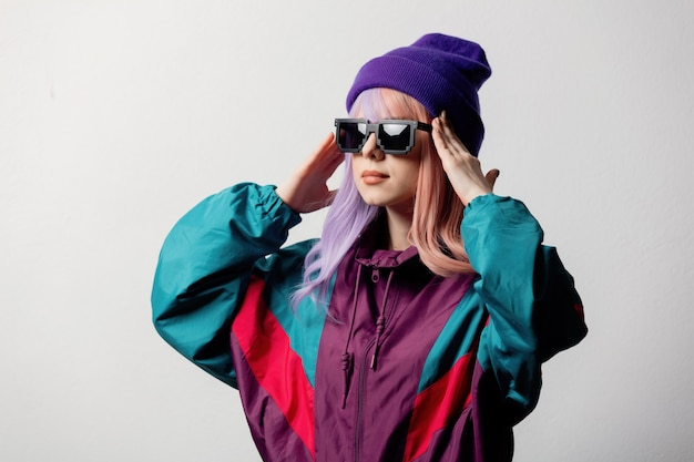 Surprised woman in sunglasses and 80s sportsuit on white background