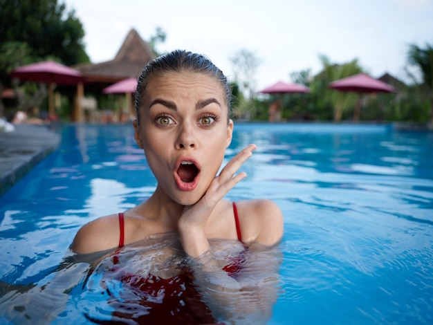 Surprised woman in swimsuit in the pool vacation island travel