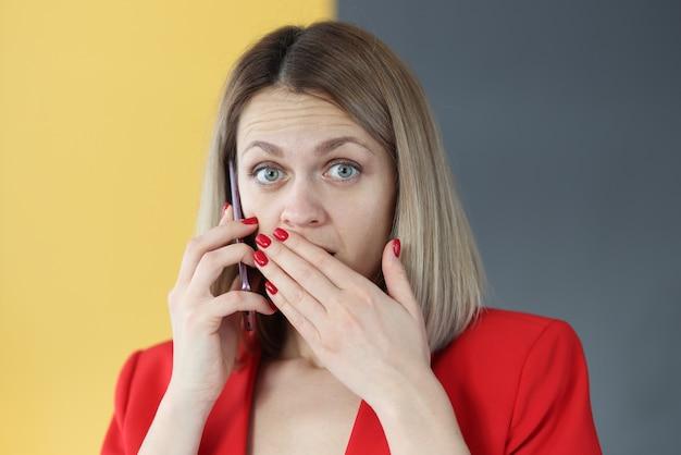 スマホで話している驚きの女性が手で口を覆っている。詐欺師の概念による盗聴