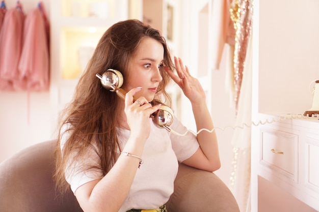 A surprised woman talks on the phone phone handset in retro style the girl in the dressing room in pink color