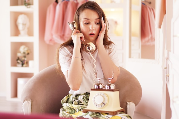 A surprised woman talks on the phone