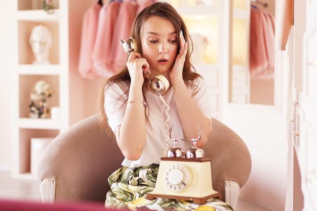 A surprised woman talks on the phone Premium Photo