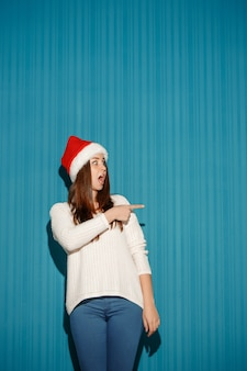 Surprised woman wearing a santa hat pointing to the right on blue background