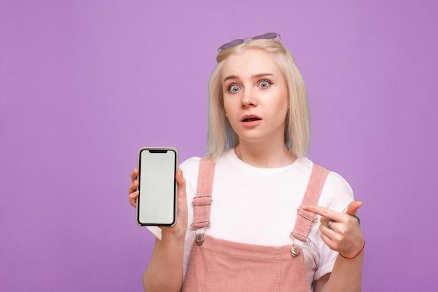 놀란 여자는 가벼운 캐주얼 옷을 입고 격리 된 스마트 폰을 보유하고 있습니다.