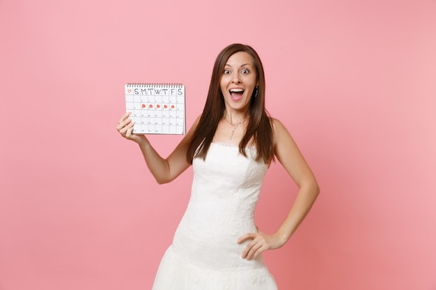 Surprised woman in white dress holding female periods calendar for checking menstruation days