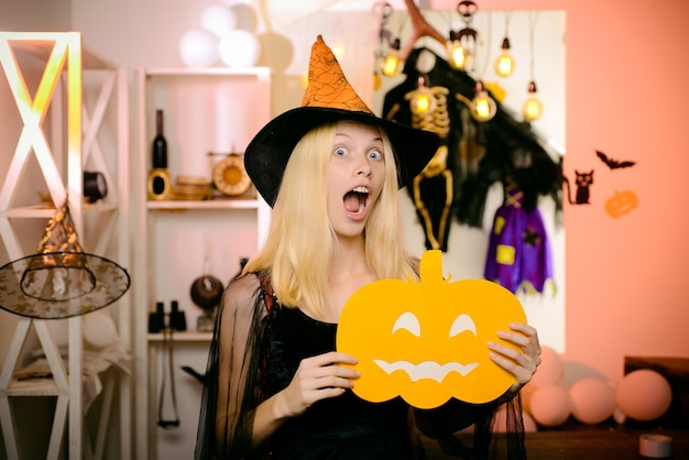 Surprised woman in witches hat and short dress. vampire halloween woman portrait. beautiful young surprised woman in witches hat and costume holding pumpkin. funny face. crazy people.