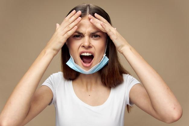 Удивленная женщина с медицинской маской на подбородке, широко открытым ртом и руками