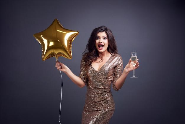 Donna sorpresa con palloncino e flûte di champagne