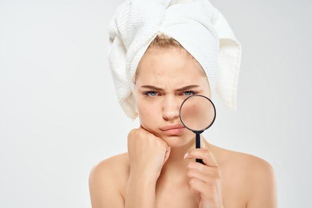 裸の肩を持つ驚いた女性は、手の健康上の問題でガラスの拡大鏡をきれいにします