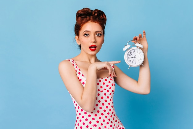 時間を示す明るい化粧で驚いた女性。青いスペースに時計を保持しているショックを受けたピンナップガールのスタジオショット。