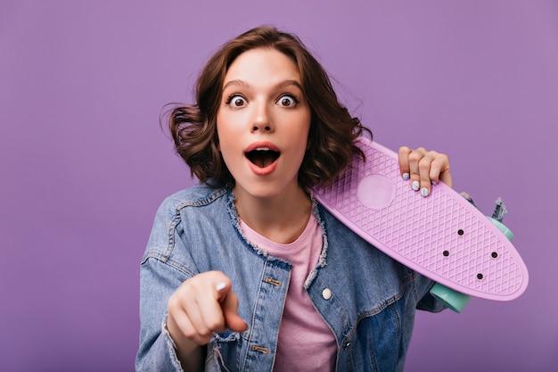 スケートボードを保持している茶色のウェーブのかかった髪の驚きの女性。驚きを表現する感情的な白人の女の子。