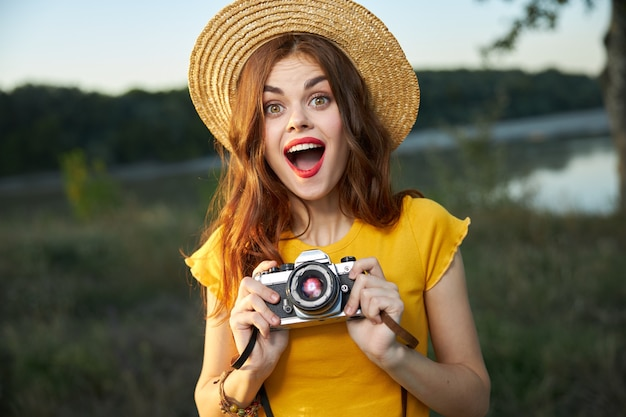 Surprised woman with camera wearing a summer hat