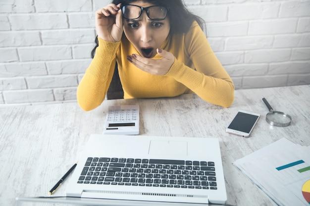 オフィスのテーブルにコンピューターを持つ驚いた女性