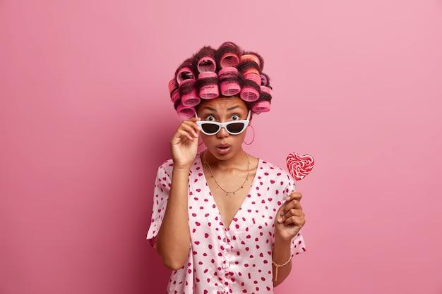 머리카락에 curlers가있는 놀란 여성은 여성의 날을 준비하고 화려한 모습을 원하며 목욕 가운과 선글라스를 착용하고 맛있는 식욕을 돋우는 롤리팝을 들고 분홍색 벽 위에 절연되어 있습니다.