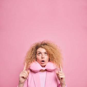곱슬곱슬한 머리를 가진 놀란 여성은 복사 공간 위의 인상적인 점을 느낀다