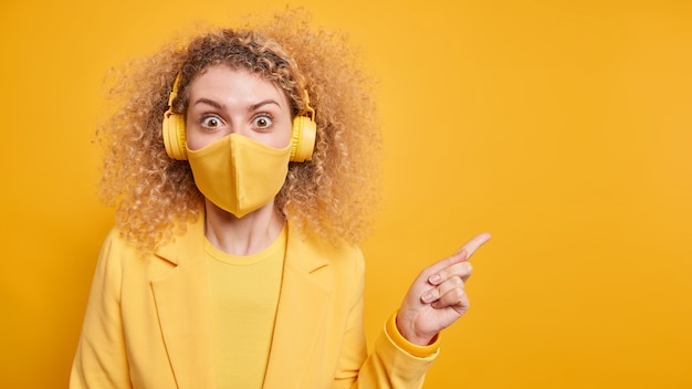 Surprised woman with curly hair indicates away on copy space beig fascinated by something amazing wears wireless headphones for listening music protective face mask during coronavirus outbreak