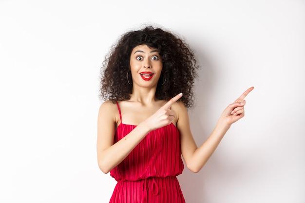 巻き毛、化粧、赤いドレスで驚いた女性、ロゴに指を向けながら驚いて幸せそうに見え、広告、白い背景を表示します。