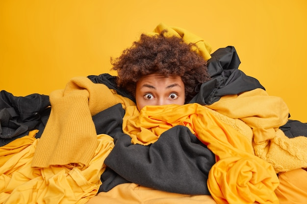 Surprised woman with curly hair stares shocked buried in big heap of yellow and black clothes does wardrobe cleaning collects clothing for washing